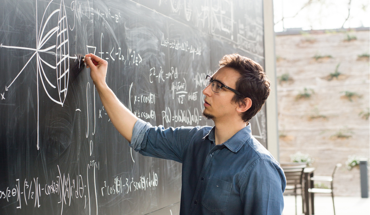 Student diagramming formulae on chalkboard